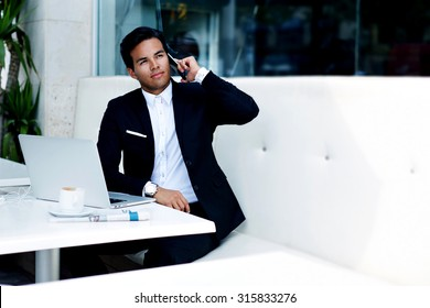 Young successful businessman in elegant suit talk on his mobile phone while sitting in modern luxury coffee shop, wealthy man having cell conversation with copy space area for text message or content