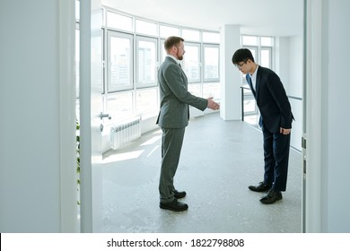 Young successful businessman in formalwear looking at his Asian business partner making bow while greeting him in corridor of office center