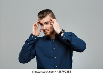 Young successful businessman having headache over grey background. Copy space.