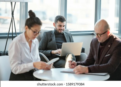 Young successful businessman with laptop surfing in the net while two business partners sitting by table near by