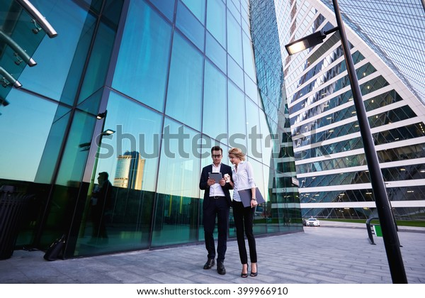 Young successful businessman in luxury suit is reading monthly report on portable digital tablet, while his female secretary with mobile phone and folder documents in hand is commenting her work