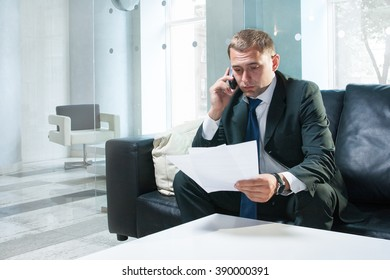 Young and successful businessman is reading documents and making a call