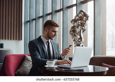 Young successful businessman sitting in lobby with his computer, talking on the phone and making useful notes. Handsome men in a suit is on a business trip abroad waiting for his business partner.