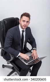 young successful businessman sitting in an office chair on a white background with a laptop on his knees.