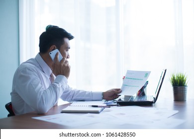 Young and successful businessman sitting at table and talking on a cell phone. Handsome man is sitting at laptop working on the table