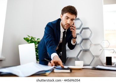 Young successful businessman speaking on phone, office background.
