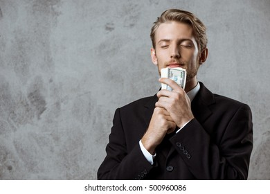 Young successful businessman in suit holding money over grey background.