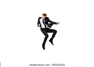 Young successful businessman in suit rejoicing, jumping over white background.