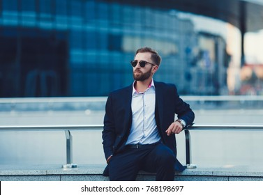 Young successful businessman in a suit sits on the background of an office building