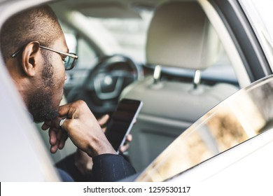 Young successful businessman talking on the phone sitting in the backseat of a expensive car. Negotiations and business meetings.