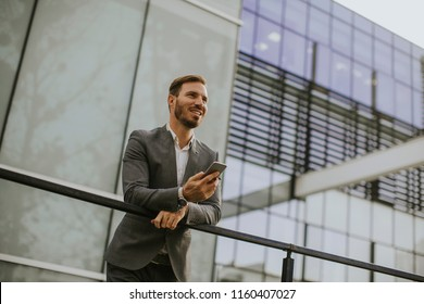 Young successful businessman wearing grey suit and holding his smartphone while standing near modern office or skyscrapers