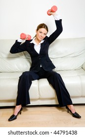 Young successful businesswoman with dumbbells