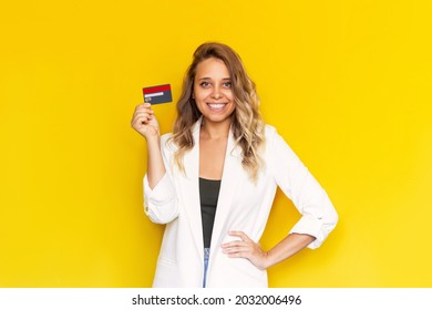 A young successful charming smiling blonde woman in a white jacket holding a plastic credit card in her hand isolated on a color yellow background. Shopping, payment for purchases, banking operations