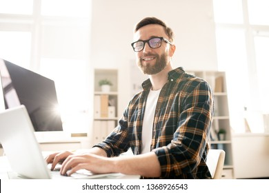 Young successful computer developer sitting by desk in front of laptop display while looking through data and looking at you