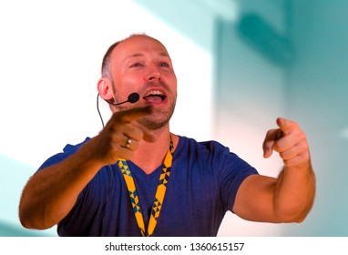 young successful and confident casual speaker man with headset speaking at corporate business convention coaching at auditorium conference room talking business success training on speaker stage