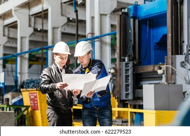 A young successful engineer discusses technical documentation with his help in the territory of a modern plant