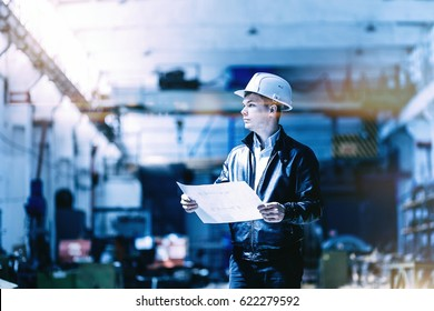 A young successful engineer with a drawing in his hands is standing in the territory of a modern factory. blue toned image