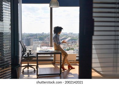 Young successful female African American executive manager ceo sitting on desk reading financial report in modern office in high floor corporate building with panoramic urban megapolis city view.