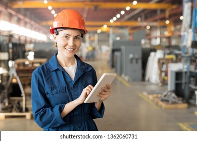 Young successful female engineer of large industrial plant surfing in the net while standing in front of camera