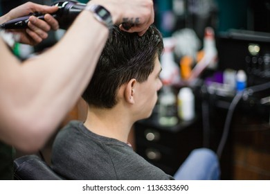 A young successful hairdresser, making an attractive man's haircut in a hairdresser. to cut long hair. man's haircut