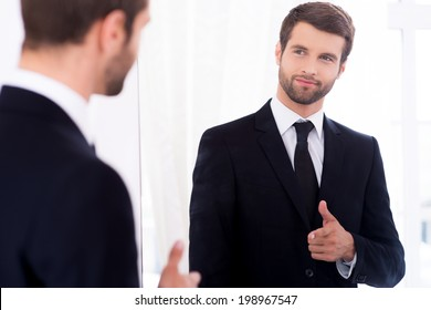 Young and successful. Handsome young man in full suit pointing himself and smiling while standing against mirror