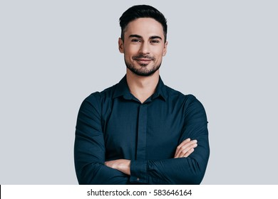 Young and successful. Handsome young man in shirt keeping arms crossed and smiling while standing against grey background