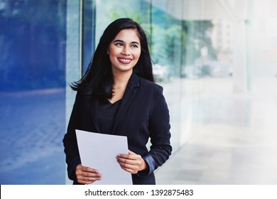 Young successful indonesian woman holding documents while standing outside the office building