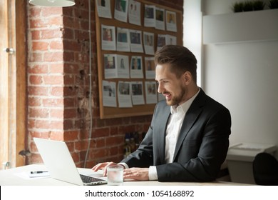 Young successful male CEO reading promising financial reports and stock exchange news using laptop in loft office. Concept of prosperous business, hardworking and rewarding. Broker monitoring rate