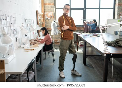 Young successful male fashion designer or tailor with prosthetic leg standing by workplace