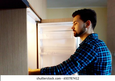 Young and successful male looks in the fridge