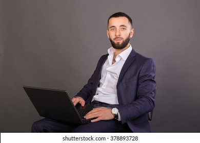 Young, successful man in a business suit with a laptop in the hands