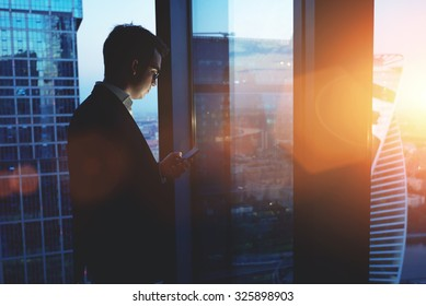 Young successful man entrepreneur mobile phone while standing in skyscraper office interior at sunset, intelligent male professional worker holding digital tablet while resting after business meeting