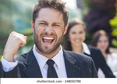 A young successful man, male executive businessman fist raised celebrating cheering shouting in front of his female business team colleagues