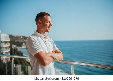 Young successful man relaxing on the hotel balcony. Happiness and leisure at the seaside