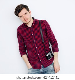 Young and successful man stands near white wall and holds a mirrorless camera