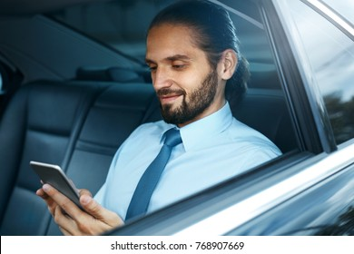 Young Successful Man Working On Phone Sitting In Car. Portrait Of Handsome Smiling Businessman In Formal Clothes Using Phone Riding To Work On Back Seat Of Luxury Business Car.  High Quality Image.