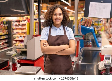 Young successful mixed-race sales clerk in workwear crossing her arms by chest while standing by cash register in supermarket