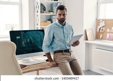 Young and successful. Young modern businessman looking at camera and using digital tablet while working in the office