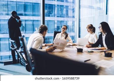 Junge erfolgreiche Unternehmen aus verschiedenen Bereichen diskutieren Dokumente mit Diagrammen und lächeln mit großen finanziellen Ergebnissen zufrieden, während sie am Konferenztisch gegen Fenster sitzen