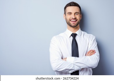 Young and successful. Portrait of handsome young man in shirt and tie keeping arms crossed and smiling while standing against grey background