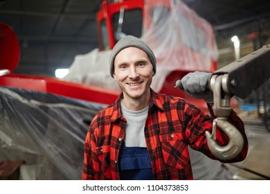 Young successful shipbuilding engineer in workwear holding by detail of large machine