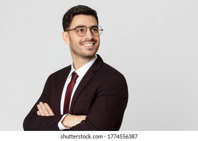 Young successful smiling businessman or CEO, cheif executive officer with crossed arms looking away, isolated on gray background
