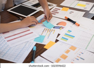 young successful startup team on meeting in modern office. businessman & businesswoman brainstorm, make a business plan, work on tablet with financial and marketing graph and chart at workplace