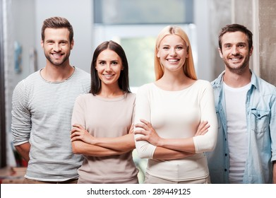 Young and successful team. Four young business people in smart casual wear standing close to each other and smiling discussing