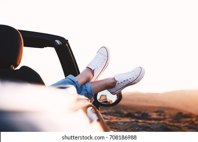 Young and successful traveler girl enjoy view and mountain landscape in sunlight from convertible car by hanging out her legs