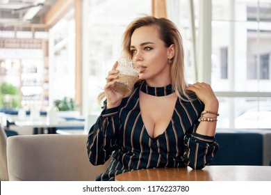 A Young, successful woman having a drink sitting at a table in a modern cafe while waiting her partner. Sensual blouse with decolletage, beautiful face and skin. Hands holding a beautiful glass.