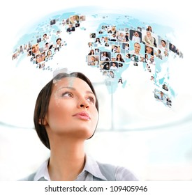 Young successful woman looking at worldmap with profile photos of her colleagues. International communication concept.