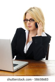 Young successful woman working at desk with laptop and mobile phone isolated on white