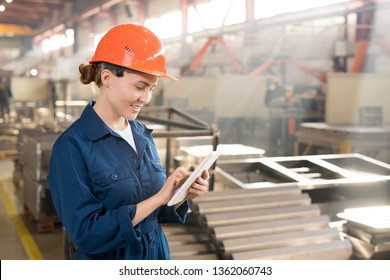 Young successful worker of contemporary factory in workwear and helmet scrolling in touchpad while searching for technical data