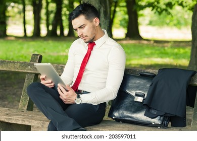 Young and successful worried business man sitting on the park bench holding a tablet